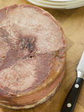Piece of Cooked Ox Tongue. On a table with a knife Royalty Free Stock Images
