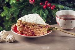Piece of cranberry cake covered with white cream on plate on the background of the Christmas tree. A piece of cranberry cake covered with white cream on plate on Royalty Free Stock Image