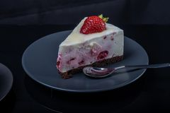 A piece of cream fruit cake decorated with strawberries on a black glass table stock photography
