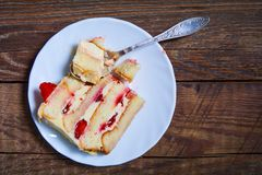 Piece of a creamy pie with strawberry on a plate Stock Images
