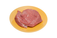 Piece of crude meat on a plate Stock Images