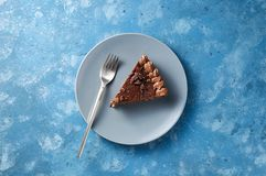 Piece of dark chocolate cake with buttercream, nuts and berry jam. On blue background. Close up top view with copy space royalty free stock photo