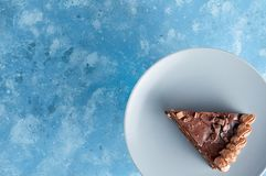 Piece of dark chocolate cake with buttercream, nuts and berry jam. On blue background. Close up top view with copy space royalty free stock images