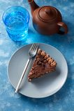 Piece of dark chocolate cake with buttercream, nuts and berry jam. Clay teapot and glass of water on blue background. Close up top view stock images