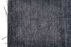 Piece of dark jeans fabric. Isolated on white background. Rough uneven edges royalty free stock photos