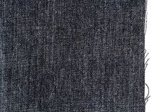 Piece of dark jeans fabric. Isolated on white background. Rough uneven edges stock image