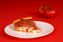 A piece of deep dish pizza with tomatoes Stock Photo