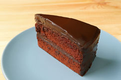 Piece of Delectable Chocolate Layer Cake Served on Blue Plate. On the Wooden Table stock photos