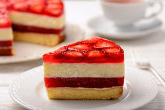 Piece of delicious cheesecake with strawberry mousse, strawberry jelly and strawberries. Royalty Free Stock Image