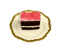 Piece of a delicious chocolate cake with icing on a decorative plate royalty free stock photography