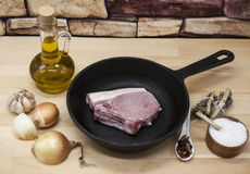 A piece of delicious fresh raw pork close-up on a cast-iron frying pan, onions, garlic, spices, salt, olive oil on rustic kitchen Stock Photos
