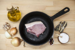A piece of delicious fresh raw pork close-up on a cast-iron frying pan, onions, garlic, spices, salt, olive oil on rustic kitchen Royalty Free Stock Image