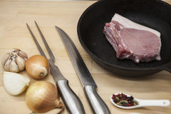 A piece of delicious fresh raw pork close-up fork, knife,spice, onion, garlic,  on a cast iron skillet on the table rustic kitchen.  Stock Photos