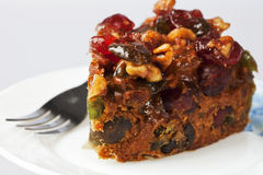 Piece of Delicious Fruit and Nut Cake. By a Fork on a Plate Royalty Free Stock Images