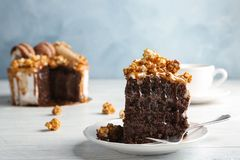 Piece of delicious homemade cake with caramel sauce. And popcorn on table Royalty Free Stock Image