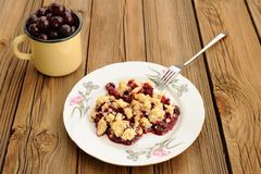 Piece of delicious homemade cherry crumble with fork in white pl. Ate with pink carnations and yellow cup with fresh cherries on wooden table horizontal Royalty Free Stock Photography
