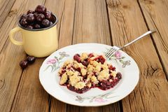 Piece of delicious homemade cherry crumble with fork in white pl. Ate with pink carnations and yellow cup with fresh cherries on wooden table horizontal Stock Photo