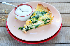 Piece of delicious quiche with smoked salmon and sour cream Stock Images