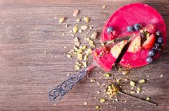 Piece of delicious raspberry cake with fresh strawberries, raspberries, blueberry, currants and pistachios on shovel. Wooden background. Free space for your Stock Photography