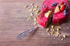 Piece of delicious raspberry cake with fresh strawberries, raspberries, blueberry, currants and pistachios on shovel. Wooden background. Free space for your Royalty Free Stock Image