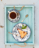 Piece of double crust plum pie and black tea in vintage porcelain cup, blue wooden tray. Top view . Royalty Free Stock Photography