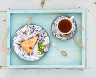 Piece of double crust plum pie and black tea in vintage porcelain cup, blue wooden tray. Top view, horizontal Royalty Free Stock Photography
