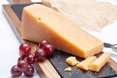 Piece of hard matured 3 years old dark yellow cheese close up stock images