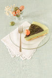 Piece of easter cake with tea matcha decorated chocolate ganache and sweet-stuff eggs on glass plate Royalty Free Stock Images