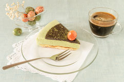 Piece of easter cake with tea matcha decorated chocolate ganache and sweet-stuff eggs on glass plate. From series elegant desserts Stock Photo