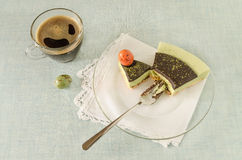 Piece of easter cake with tea matcha decorated chocolate ganache and sweet-stuff eggs on glass plate Stock Photos