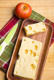 A piece of emmethal swiss cheese over a wooden rustic plate, a g Royalty Free Stock Images