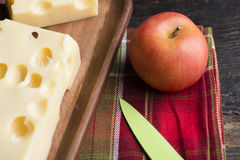 A piece of emmethal swiss cheese over a wooden rustic plate, a g Stock Photo