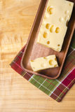 A piece of emmethal swiss cheese over a wooden rustic plate, a g Royalty Free Stock Photos