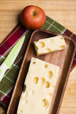 A piece of emmethal swiss cheese over a wooden rustic plate, a g Stock Photography