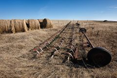 Farm equipment and hay bales. Royalty Free Stock Photo