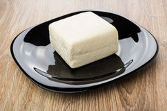 Piece of feta cheese in black plate on table Stock Photography
