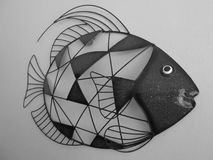 Wall Fish Art In Grey. A piece of fish art, made of metal pieces and wire, done in greys royalty free stock image