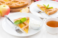 Piece of fresh apple pie with whipped cream and cup of tea Royalty Free Stock Photography
