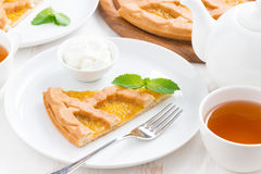 Piece of fresh apple pie with whipped cream on a plate. And black tea, close-up Stock Photos