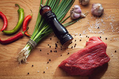 Piece of fresh beef and cooking ingredients. Still life with piece of fresh beef, pepper mill, chili, garlic and green onion Stock Images
