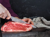 A piece of fresh beef on marble dark a wooden board. Male hand with a knife. Cutting the meat into steaks. Stock Images