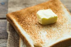 Piece of fresh butter on stacked toasted slice sandwich bread on gunny sack cloth on wooden table. Close up Stock Image