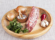A piece of fresh marbled beef, chili pepper, parsley, onion, garlic, ribs lie on a wooden tray Royalty Free Stock Photography