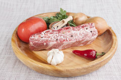 A piece of fresh marbled beef, chili pepper, parsley, onion, garlic, ribs lie on a wooden tray Royalty Free Stock Photos