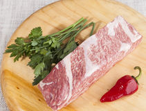 A piece of fresh marbled beef, chili pepper, parsley, ribs lie on a wooden tray Royalty Free Stock Photography