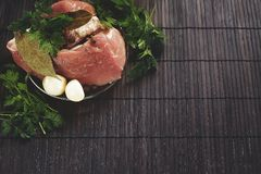 A piece of fresh meat on a plate with garlic, parsley, lautre le. Af and pepper on a wooden background. Pork or beef fillet ready for use Stock Photo