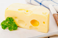 Edam cheese. Piece of fresh organic edam cheese on wooden board on breakfast kitchen table stock image