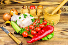 Piece of fresh pork lard, fresh produce, greens, vegetables on the wooden board and knife on table. Royalty Free Stock Photography