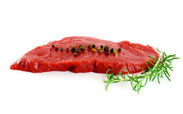 Piece of fresh raw meat with pepper, rosemary. Over white Stock Photography