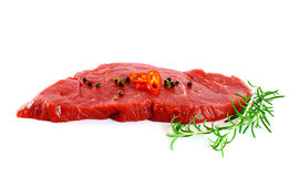 Piece of fresh raw meat with pepper, rosemary. Over white Royalty Free Stock Photo
